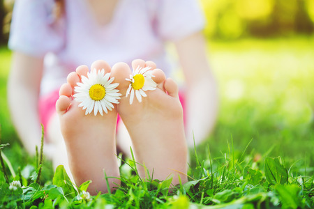 Child feet with daisy flower on green grass in a summer park.