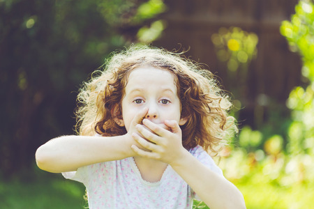 spurious: Little girl covering her mouth with her hands. Surprised or scared.