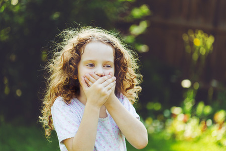 vomito: Little girl covering her mouth with her hands. Surprised or scared.