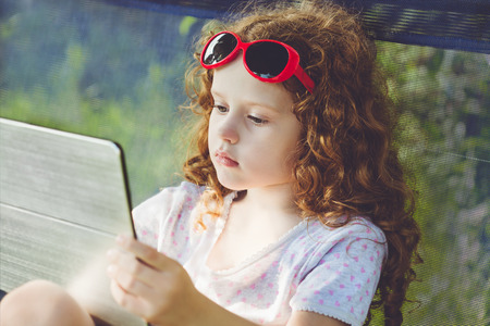 touched: Serious little girl, playing tablet pc outdoors. Stock Photo