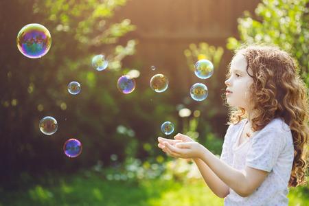 小さな女の子は、石鹸の泡をキャッチします。 写真素材 - 43614406