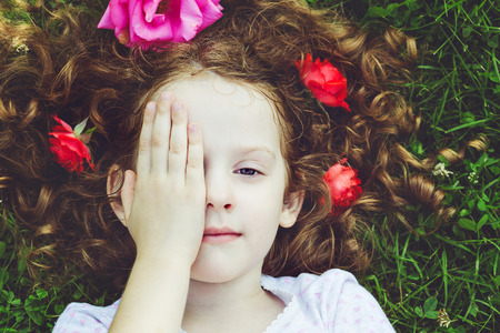 hands on head: Little girl lying on the green grass, and closed eyes with her hand. Stock Photo