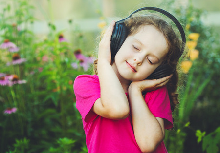 少女は目を閉じるし、ヘッドフォンで音楽を聴きます。Instagram のフィルター。 写真素材 - 44050110