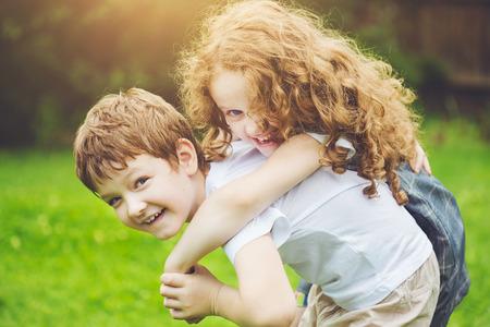 niños riendose: Niños felices con cuestas a caballo en la luz del atardecer. Las niñas se ríen. Concepto de la amistad.