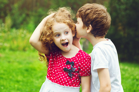 secret information: Little boy and girl whispers. Stock Photo