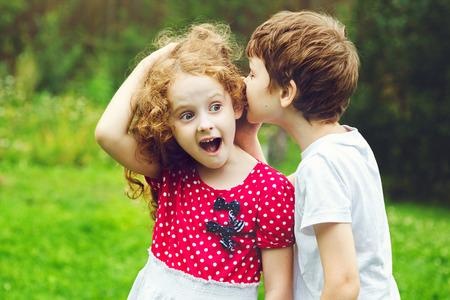 Petit garçon et fille chuchotements. Banque d'images