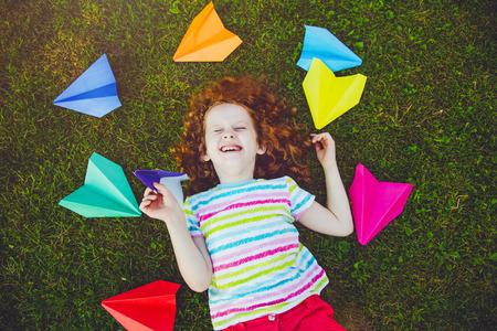 Rire fille jetant un avion en papier dans l'herbe verte au parc d'été. Banque d'images