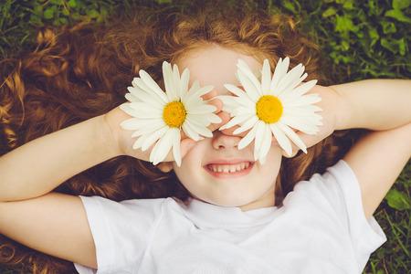 deitado: Criança com os olhos da margarida, na grama verde em um parque do verão.