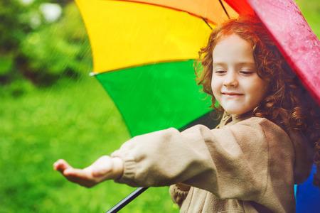 Little girl  hiding under an umbrella from the rain Stock Photo