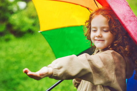 Petite fille se cachant sous un parapluie de la pluie Banque d'images