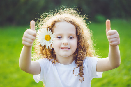 Laughing girl with daisy in her hairs, showing thumbs up. Imagens