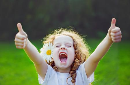 emociones: Muchacha de risa con la margarita en sus pelos, que muestra los pulgares para arriba. Foto de archivo