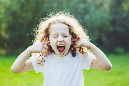 unruly: Little girl covering her ears and screams.