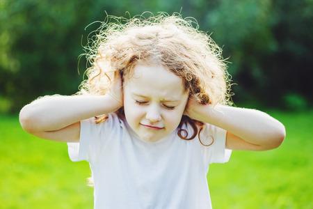 keep: Little girl covering her ears.
