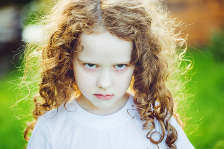 Emotional child with angry expression on face.