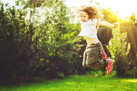 jumping: La niña salta en el aire libre. Concepto feliz infancia.