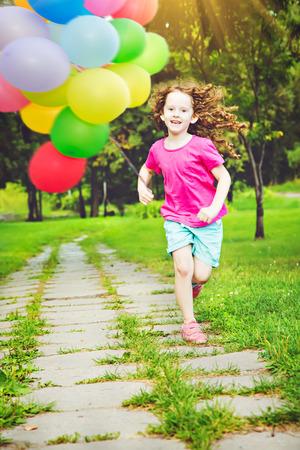 Ni�o feliz saltando al aire libre con los globos.