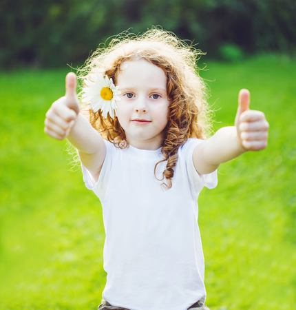 whie: Little girl with whie t-shirt, showing thumbs up. Stock Photo