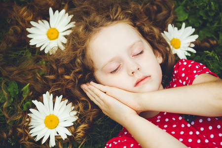 soothing: Sweet little girl sleeping on the grass with chamomiles. The soothing aroma of chamomile, natural skin care, fresh air.