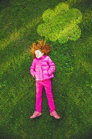 pantalones abajo: Pelirroja chica tumbada en la hierba verde en el parque bajo iluminación nube en la luz del atardecer. Alta vista superior, infancia feliz, primavera u otoño vacaciones activas. Foto de archivo