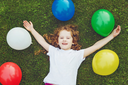 childhood: Happy child lies on green grass with rainbow balloons at summer park. Happy childhood, birthday party concept. Stock Photo