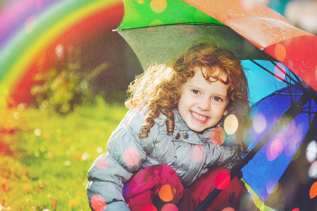 one child: Laughing girl in the rain with a rainbow and with color bokeh.  Happy and healthy childhood concept.
