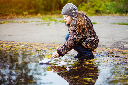 puddle: Girl runs a paper boat in the autumn park.