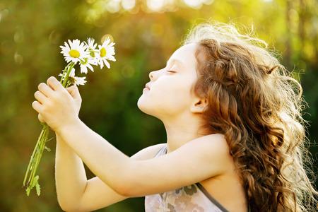 kinderen: Meisje ruiken een boeket van madeliefjes, foto in het profiel. Gezonde ademhaling. Instagram toning, zonsondergang licht. Stockfoto
