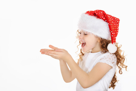 stretched: Little girl in Santa hat, stretched his hands with presenting your text or product on light background. Stock Photo