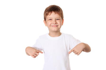CAMISAS: Niño pequeño feliz apuntando sus dedos en una camiseta en blanco, un lugar para su publicidad. Foto de archivo