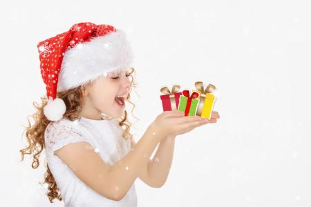 Ni�a en Santa sombrero, mantenga regalo de navidad en la mano, los copos de nieve sobre fondo claro.