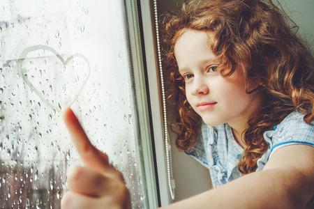 lluvia: Niño feliz dibujo corazón en la ventana. Tonificación foto para filtro de Instagram.