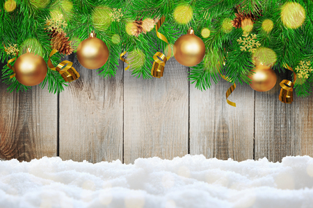 gold snowflakes: Christmas background. Green Fir tree branches with serpentine, pine cones, gold snowflakes, ball and bokeh on snow background. Stock Photo