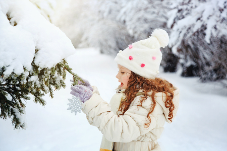 snow tree: Little girl decorates the Christmas tree.