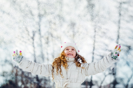 falling: Little girl looking for falling snow. Falling snow around the child. Happy childhood and freedom concept.