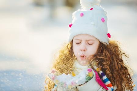La ni�a sopla nieve con manoplas, sobre un fondo bokeh copos de nieve.