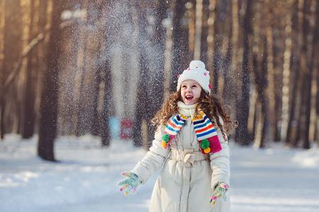 Ni�a que juega con la nieve. La ca�da de la nieve alrededor del ni�o.