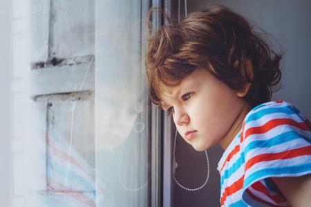 Peque�o ni�o mirando por la ventana a trav�s de las persianas. Antecedentes tonificaci�n de Instagram filtro.