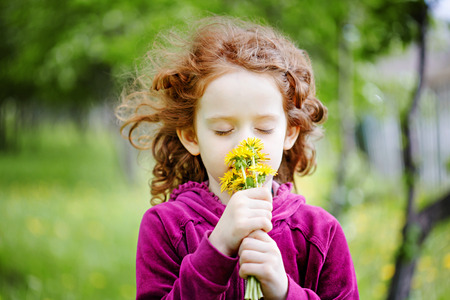 Little girl closed her eyes and breathes yellow dandelions in the field.