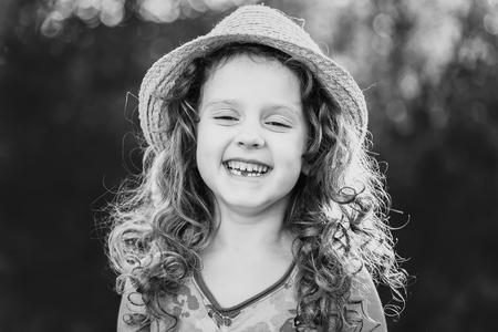 infancia: Retrato blanco y negro de una niña divertida. Niño diente que falta. Concepto feliz infancia.