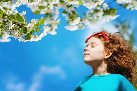 어린 소녀는 그녀의 눈을 폐쇄하고 공원에서 신선한 공기를 호흡. 스톡 콘텐츠