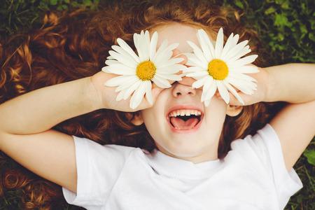 Enfant aux yeux marguerite, sur l'herbe verte dans un parc d'été.