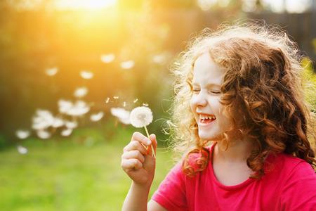 석양 빛에 민들레 불고 작은 곱슬 소녀. 인스 타 그램 필터. 건강, 의료 개념.
