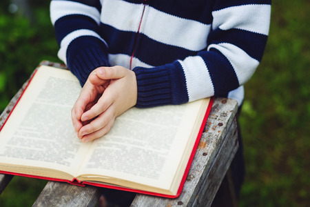 kid reading: Child hands are on folded in prayer on a Holy Bible. Concept for faith, spirituality and religion. Stock Photo