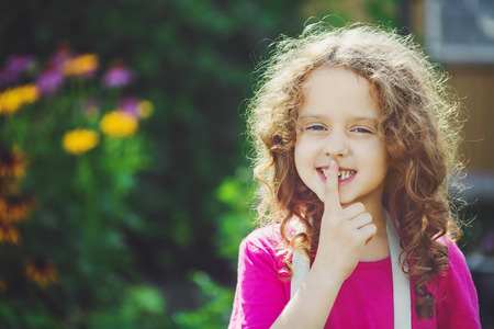 little girl putting finger up to lips and ask silence. Toning photo. Stock Photo