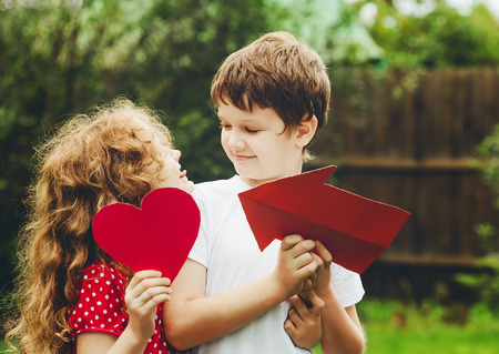 boy beautiful: Cute children embrace and holding red heart shape in summer park. Valentines day background.