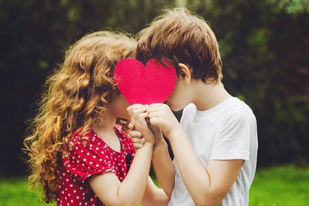 여름 공원에서 붉은 심장 모양을 들고 귀여운 아이들. 발렌타인 배경.