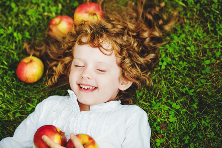 nice girl: Curly girl lies on the grass with apple and smiling. Healthy smiling and happy childhood. Soft focuse.