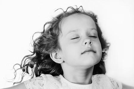 어린 소녀는 그녀의 눈을 감고 신선한 공기를 마셔. 흑백 초상화입니다.
