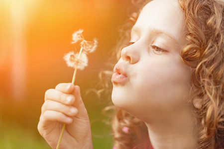 Cute little girl blowing dandelion in sunset light, toning instagram filter.